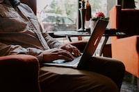 man sitting while using MacBook on lap
