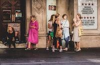 six women standing in front of store facade