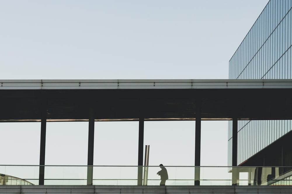 person walking on bridge with roof near building during daytime
