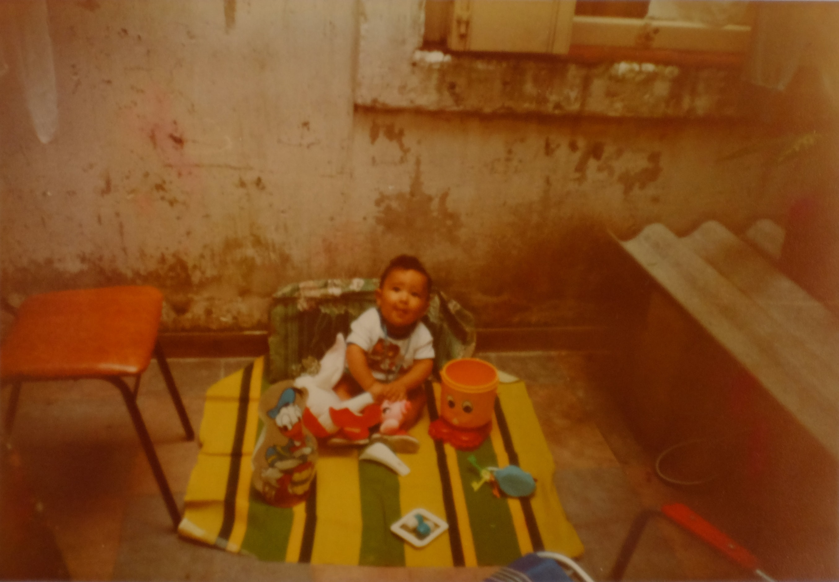 baby sitting on yellow and green textile
