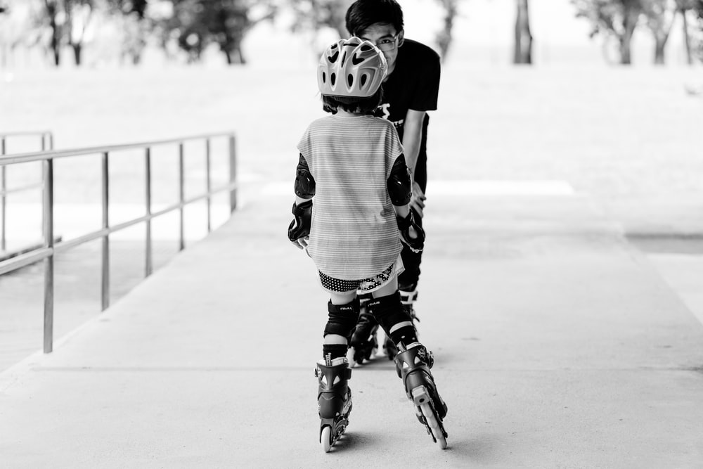 grayscale photo of man and girl using inline skates near railings