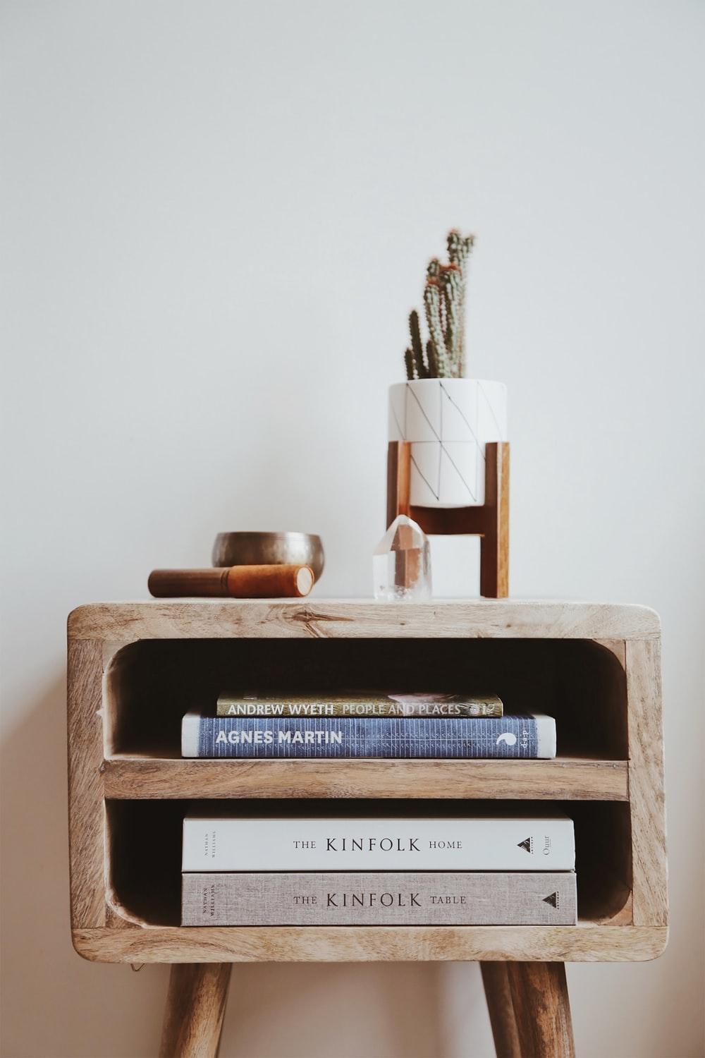 books in brown wooden side table beside white wall