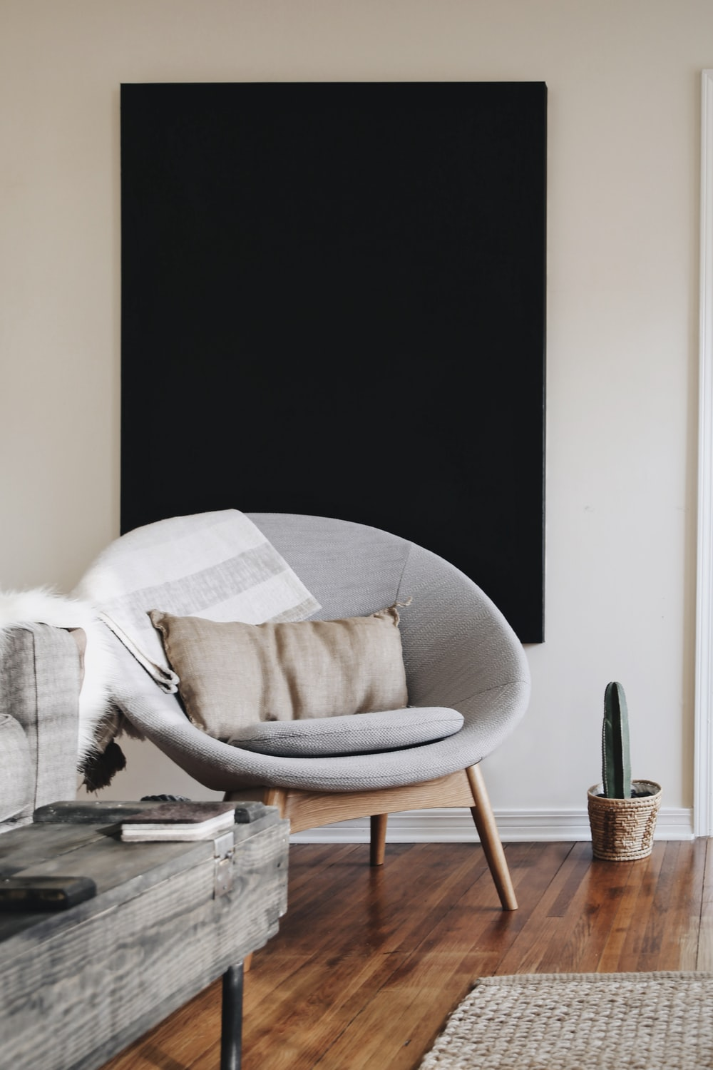 round grey moon chair with brown pillow on top