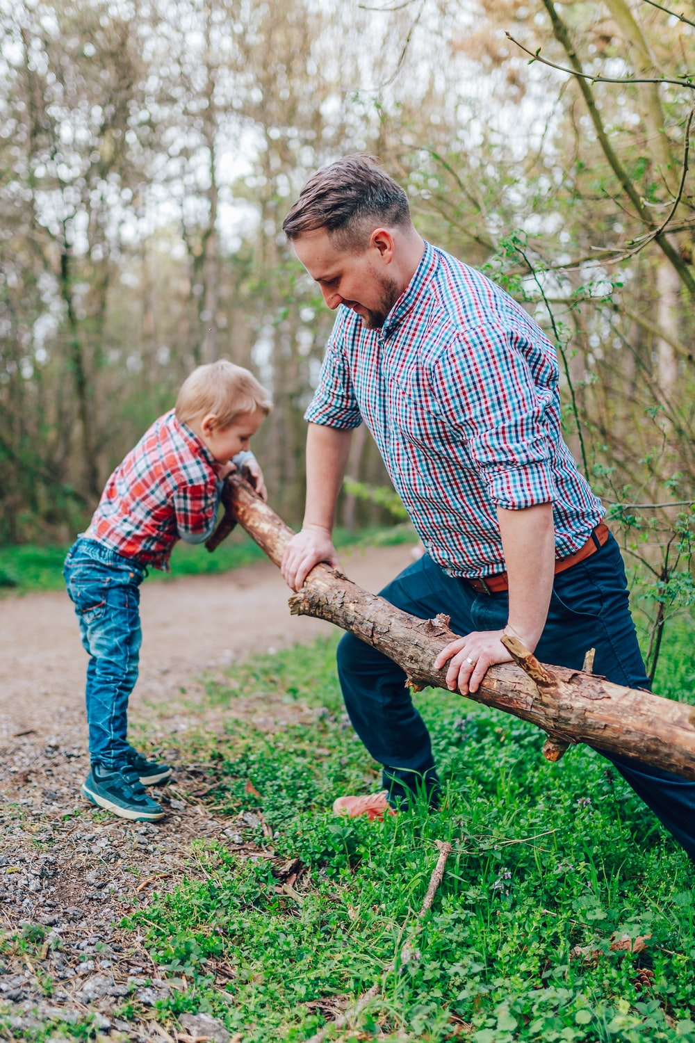 man holding tree branch in front of boy