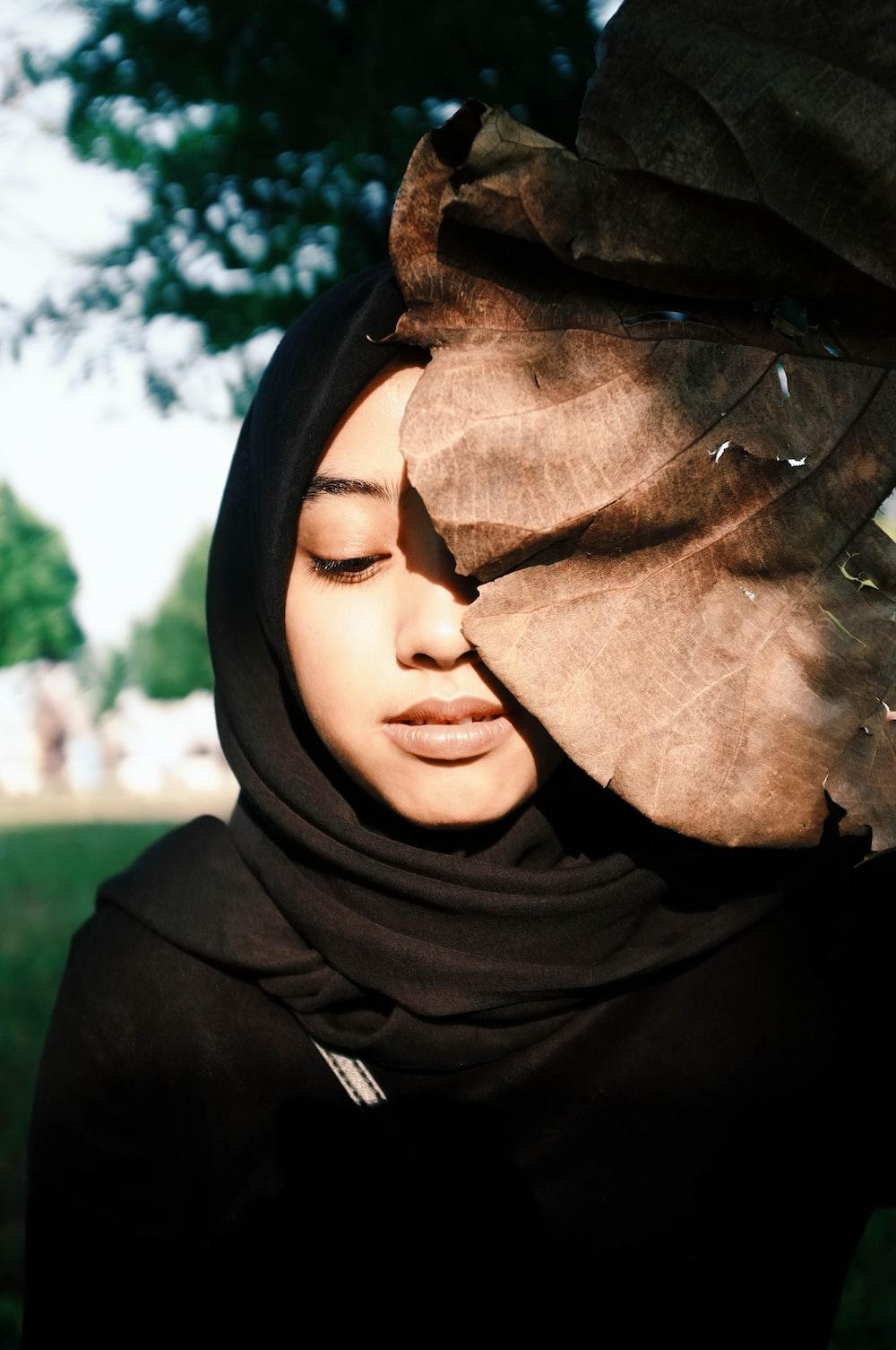 woman in black traditional dress behind dried brown leaf