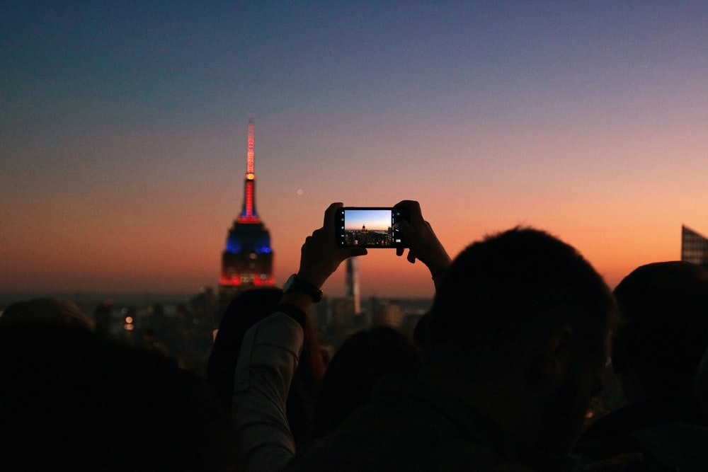 silhouette photo of man taking photo the lighted tower
