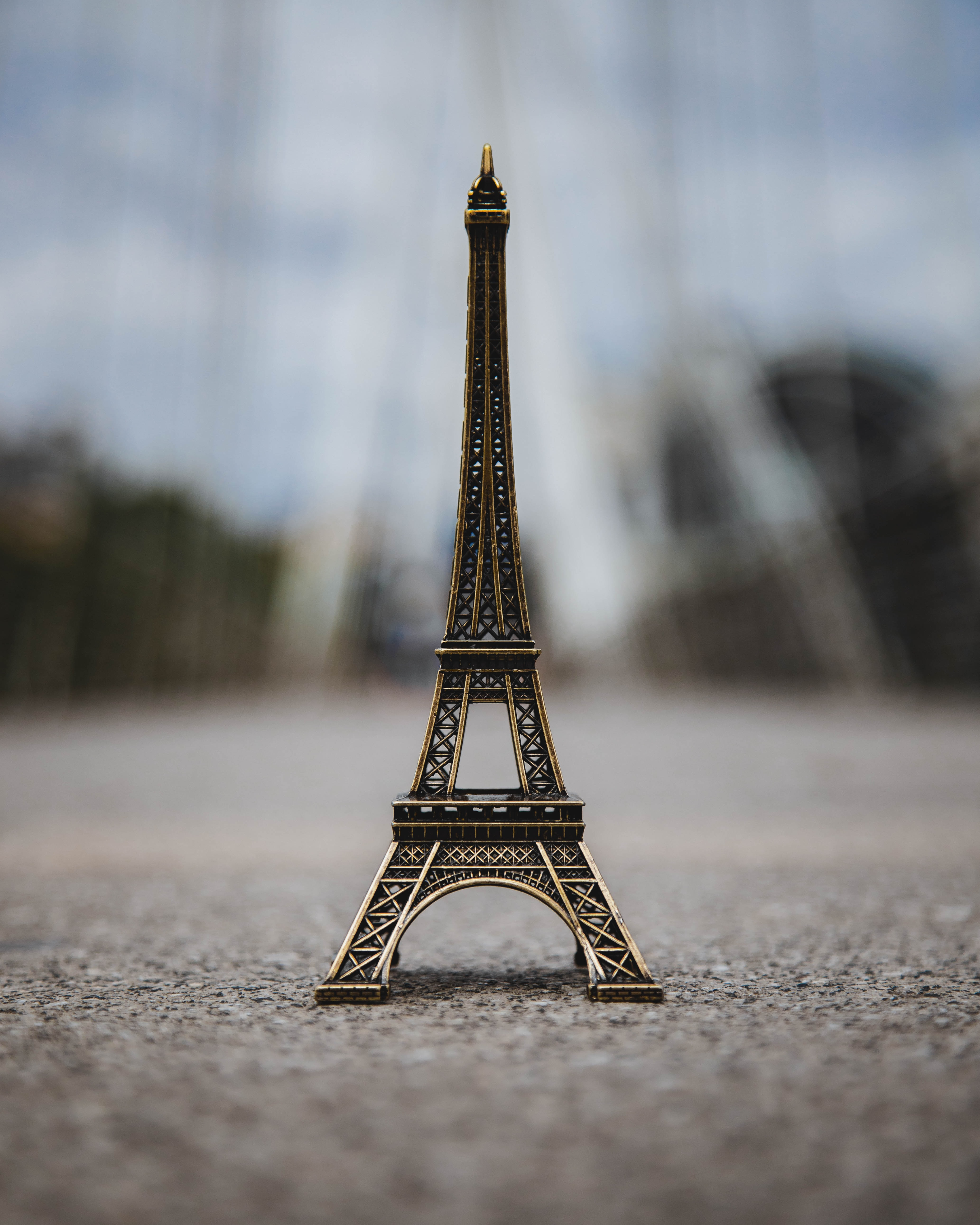 close up photography of brass-colored Eiffel Tower miniature