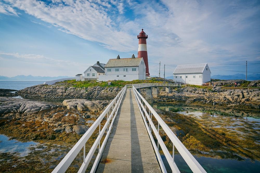 photo of suspension bridge towards into lighthouse during daytime