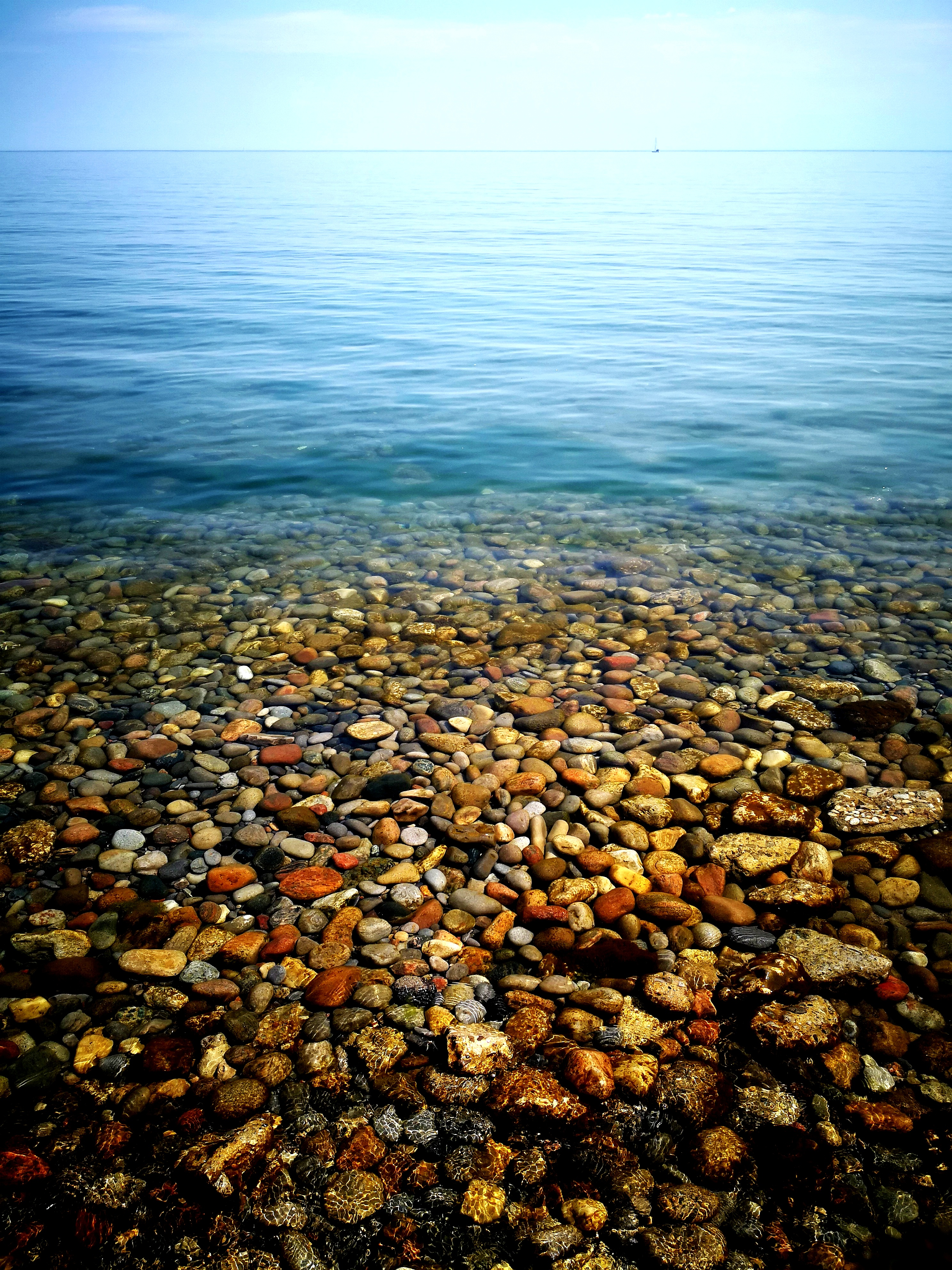 I visited Lake Ontario and saw this beautiful view. It was a sunny afternoon, the water was absolutely still and pristine clear. So clear infact, that you could see the pebbles lying below. I just clicked it.