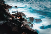 body of water smashing trough rocks