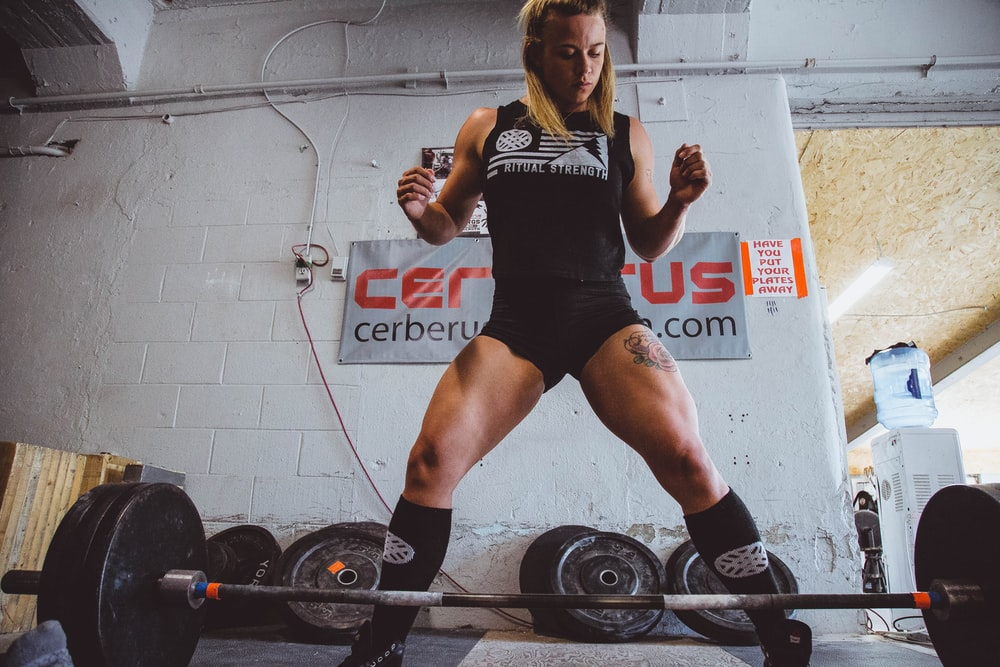 woman standing in front of black barbell