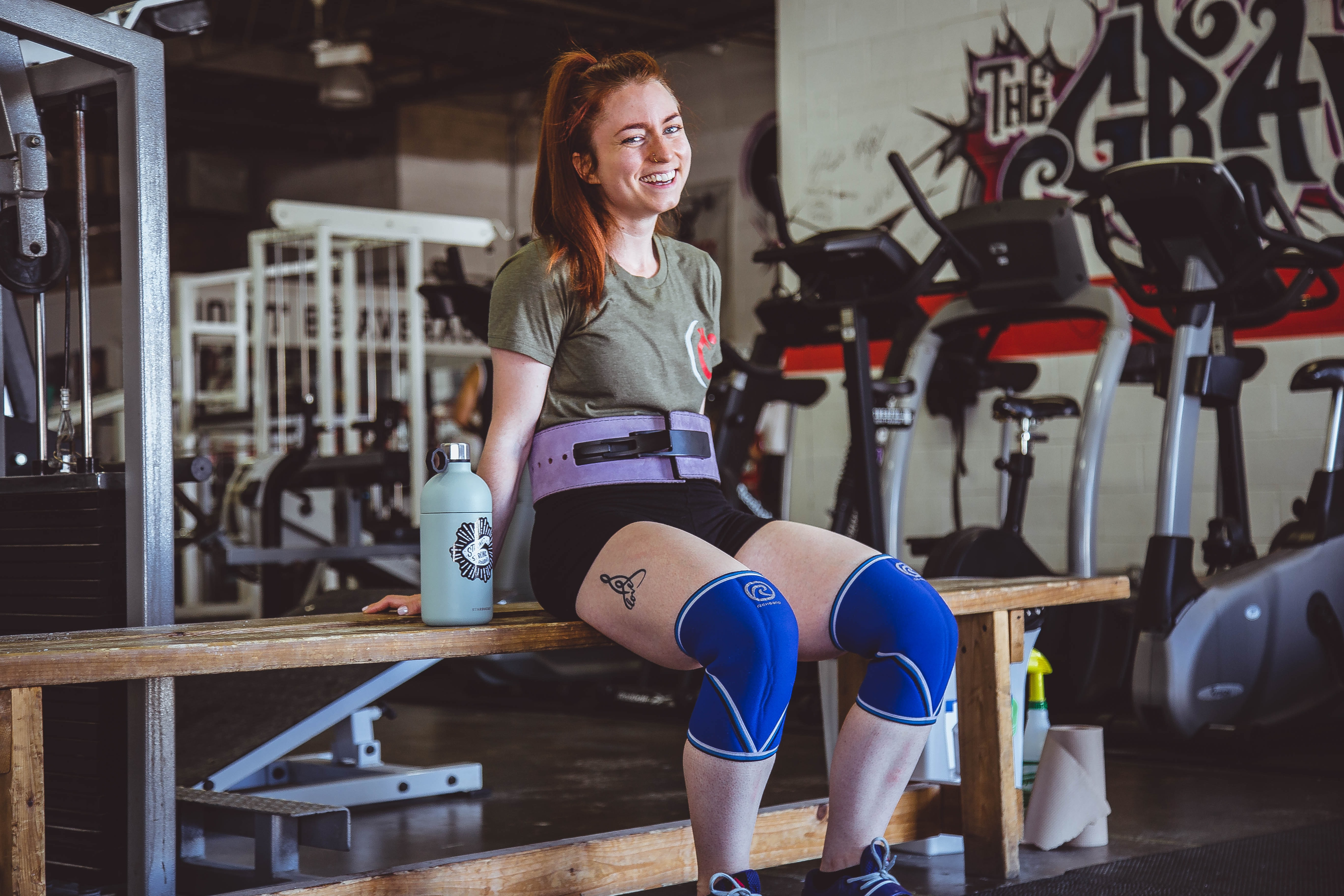 woman sitting on brown wooden bench at the gym