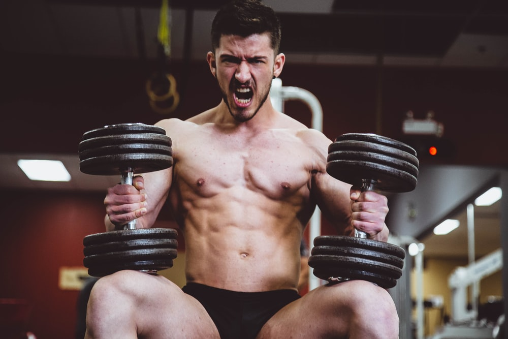 man holding two dumbbells