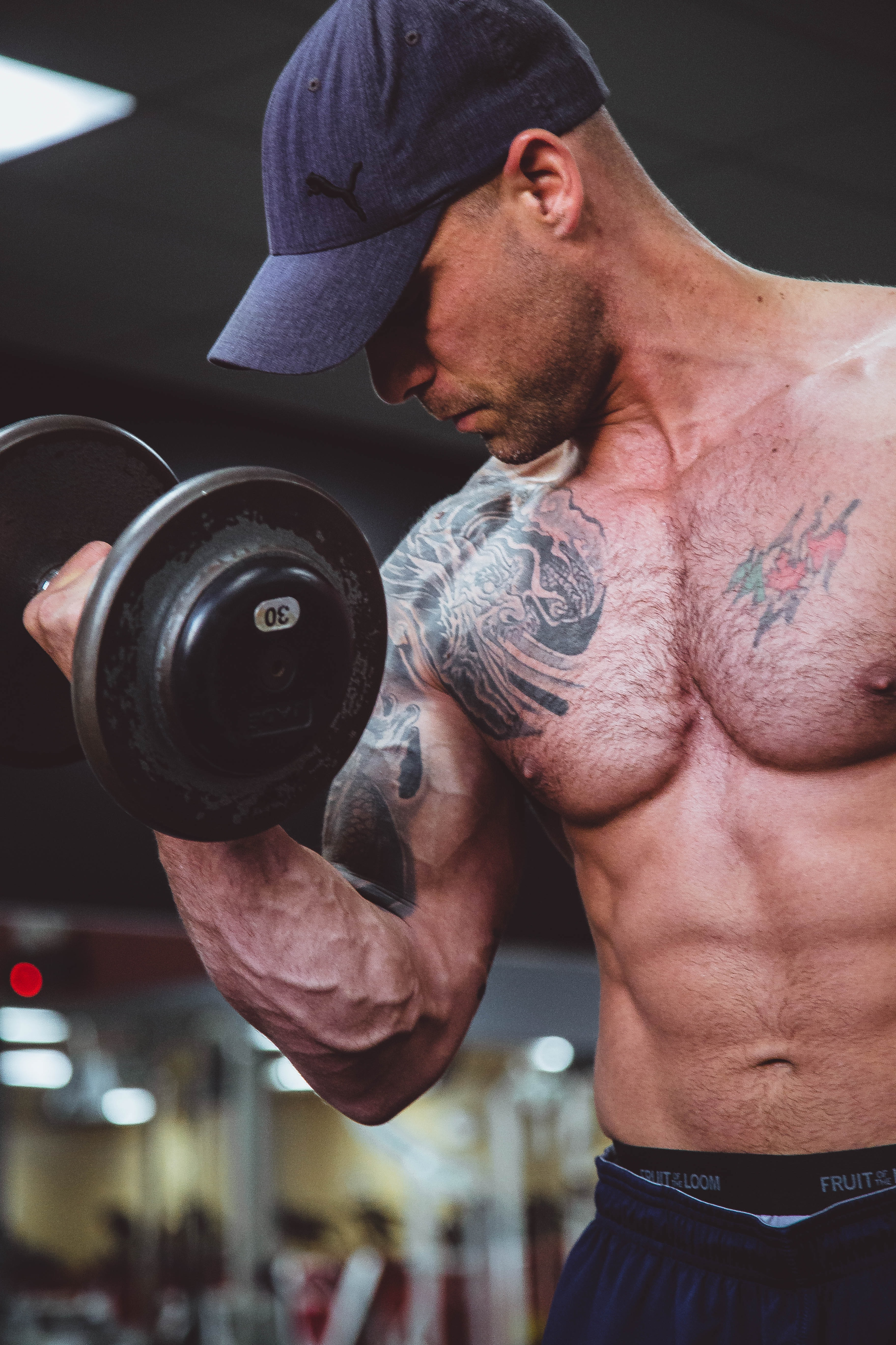 topless man holding black dumbell on right hand