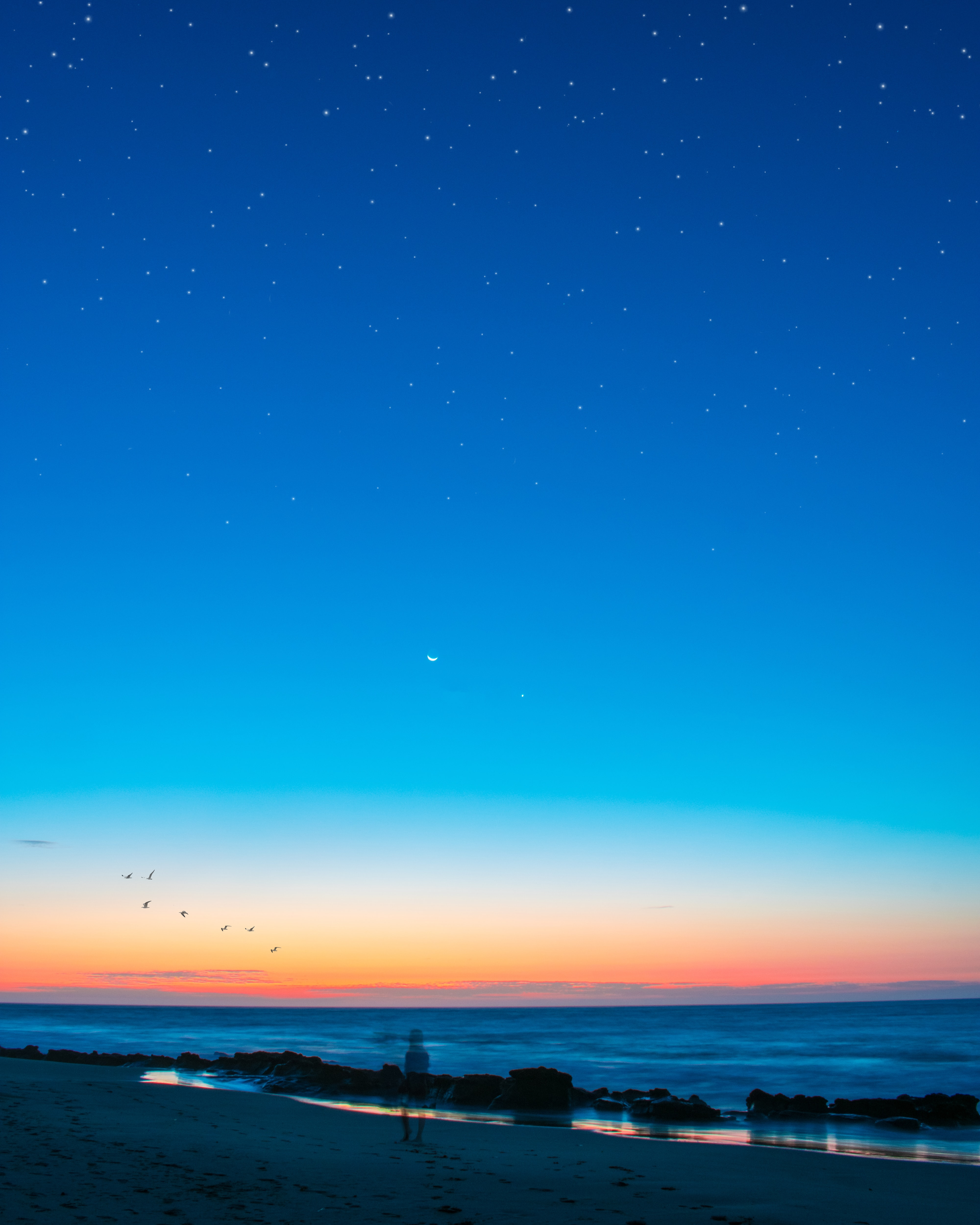 body of water under blue sky with stars