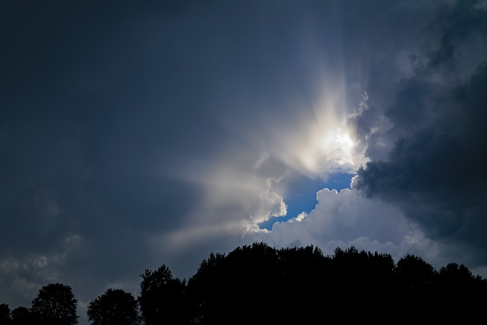 low angle photography of sun covering by clouds