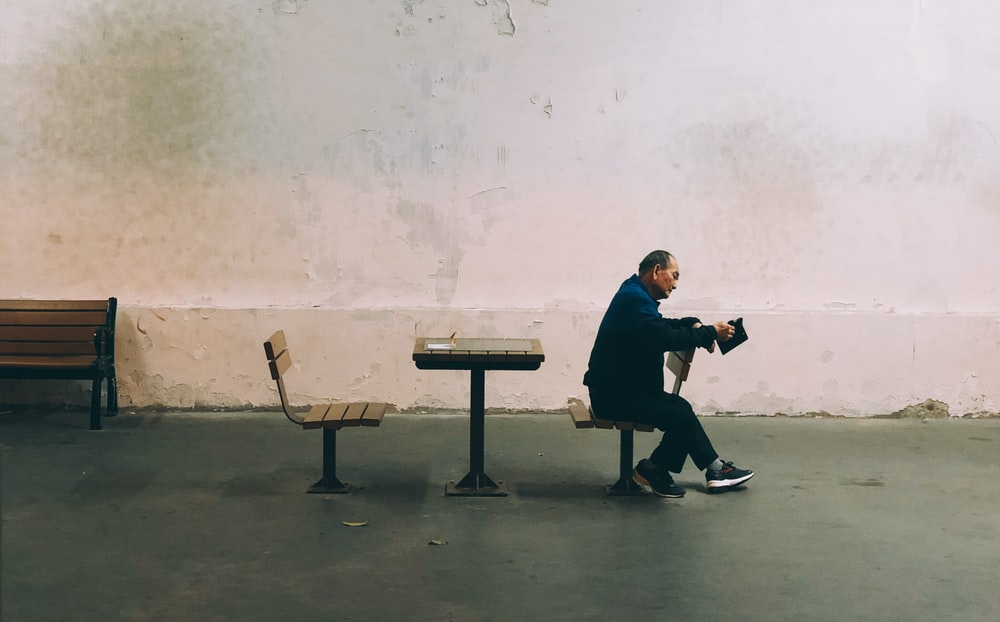 man in black coat sitting on bench