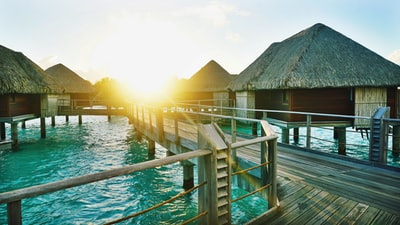 brown wooden dock between houses bora bora teams background