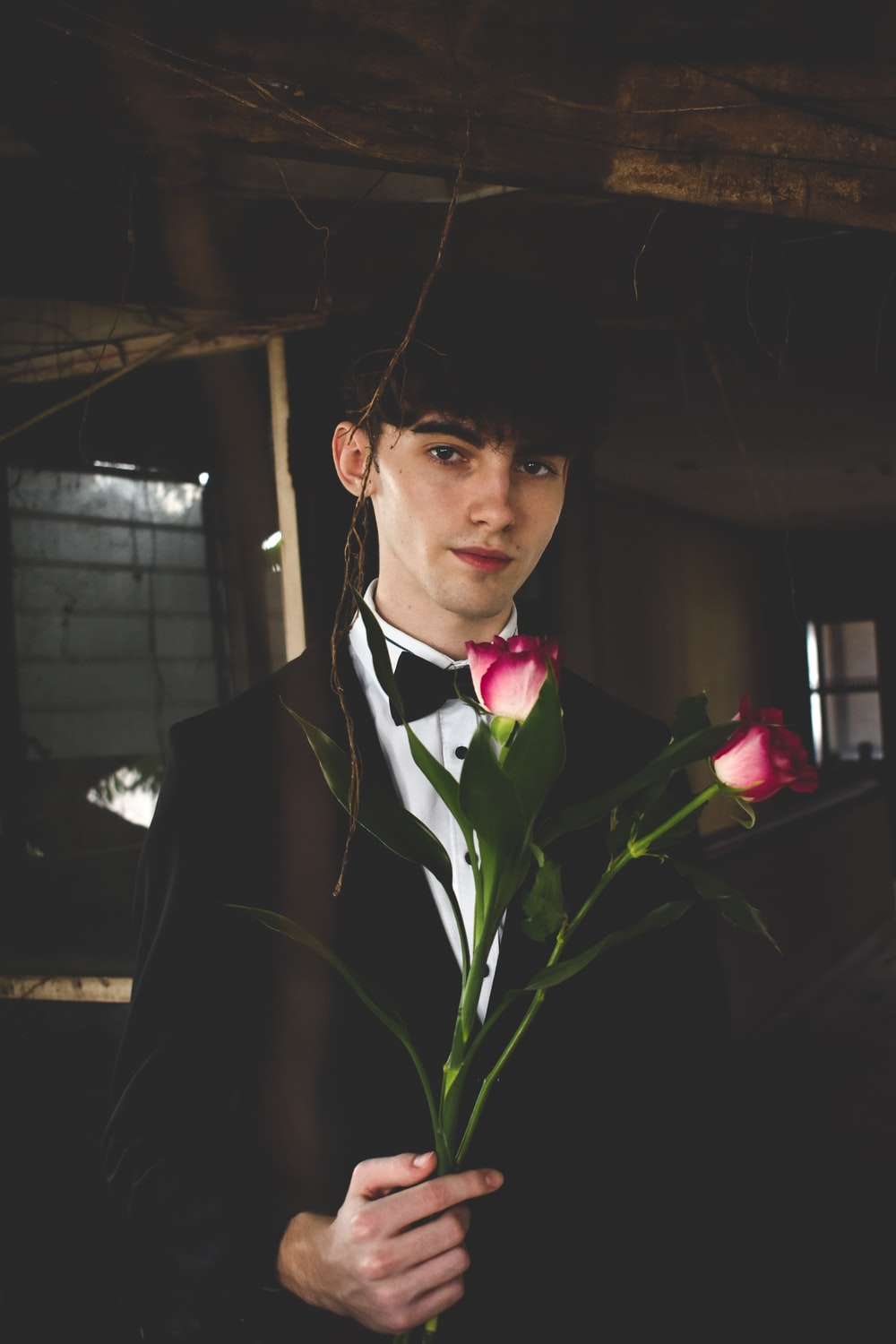 man wearing black and white formal suit holding two red roses