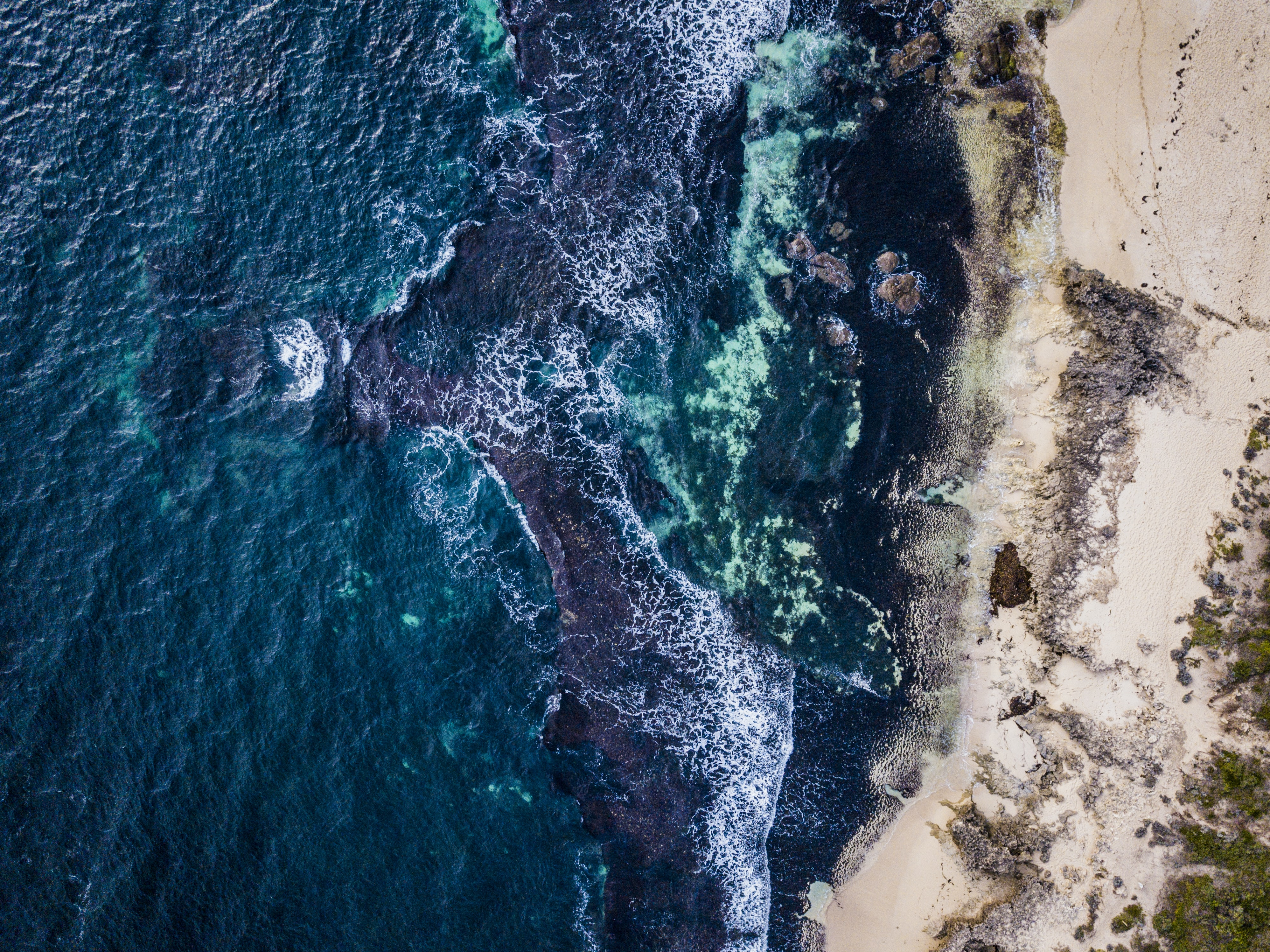 aerial photography of sea waves crashing to shore