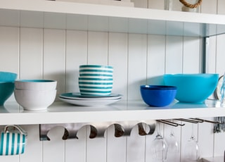 assorted ceramic food bowls on white shelf
