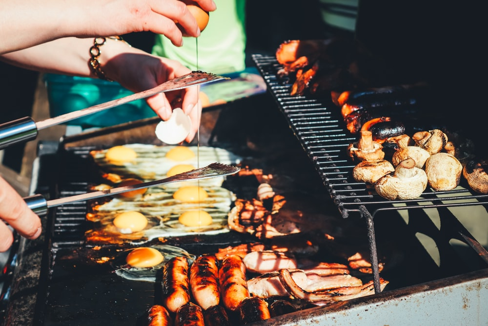 person holding tong with grilled food