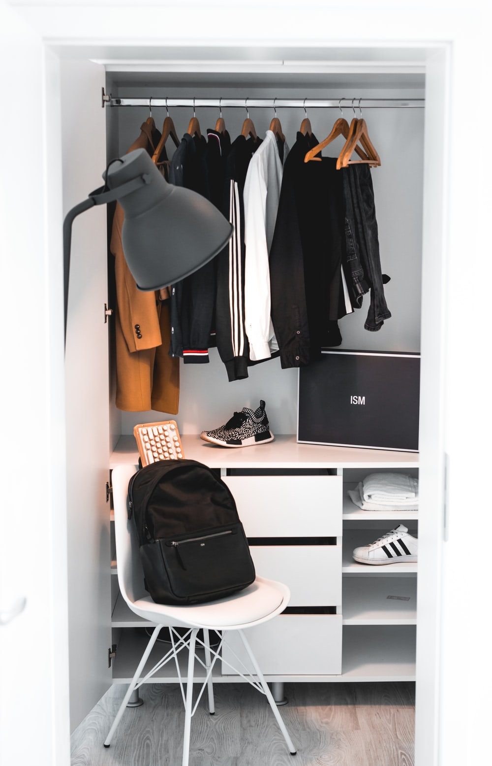 black backpack on white chair beside cabinet
