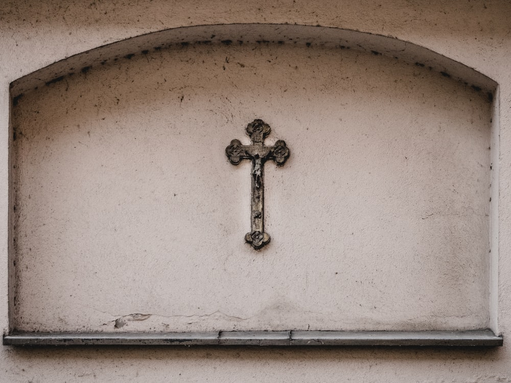 white wooden Crucifix mounted on concrete wall