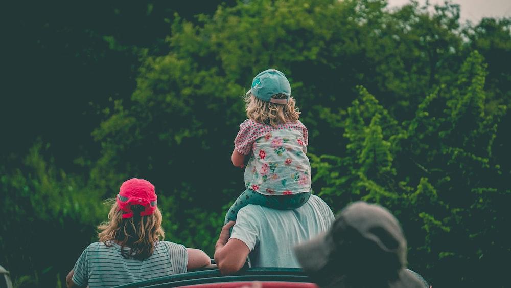 girl riding man's shoulder beside girl near trees during day