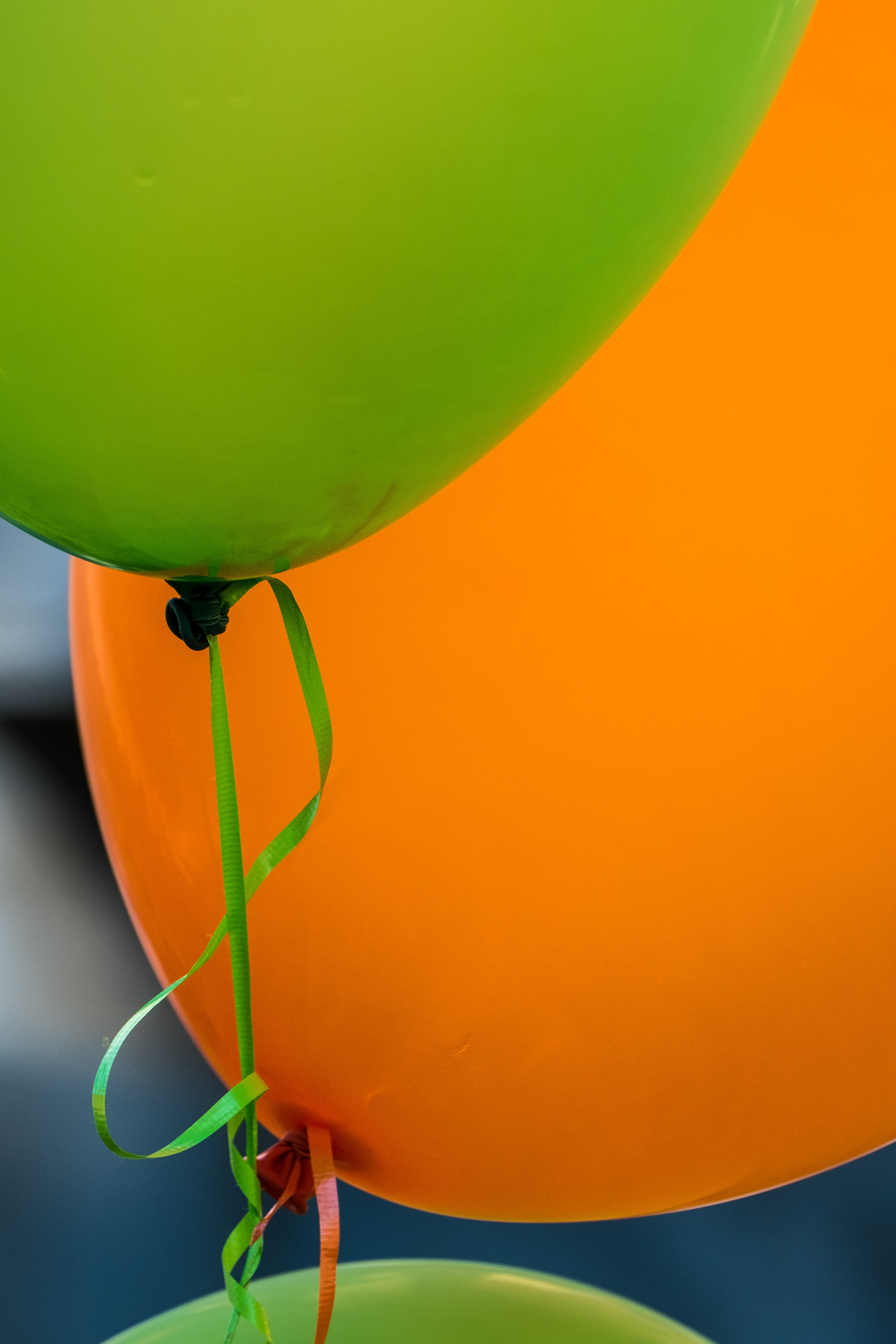 shallow focus photography of green and orange balloon