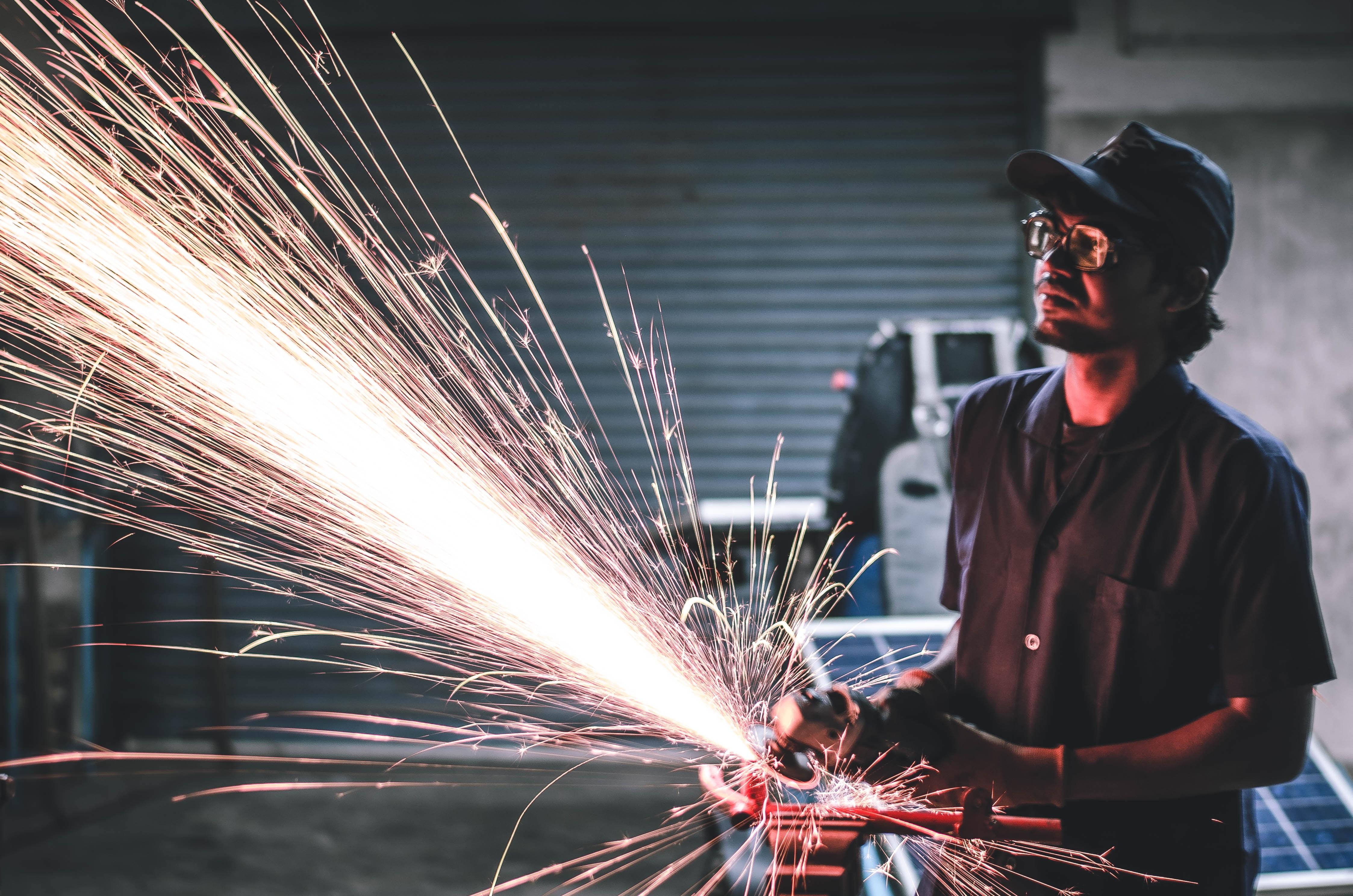 man in brown button-up shirt grinding metal