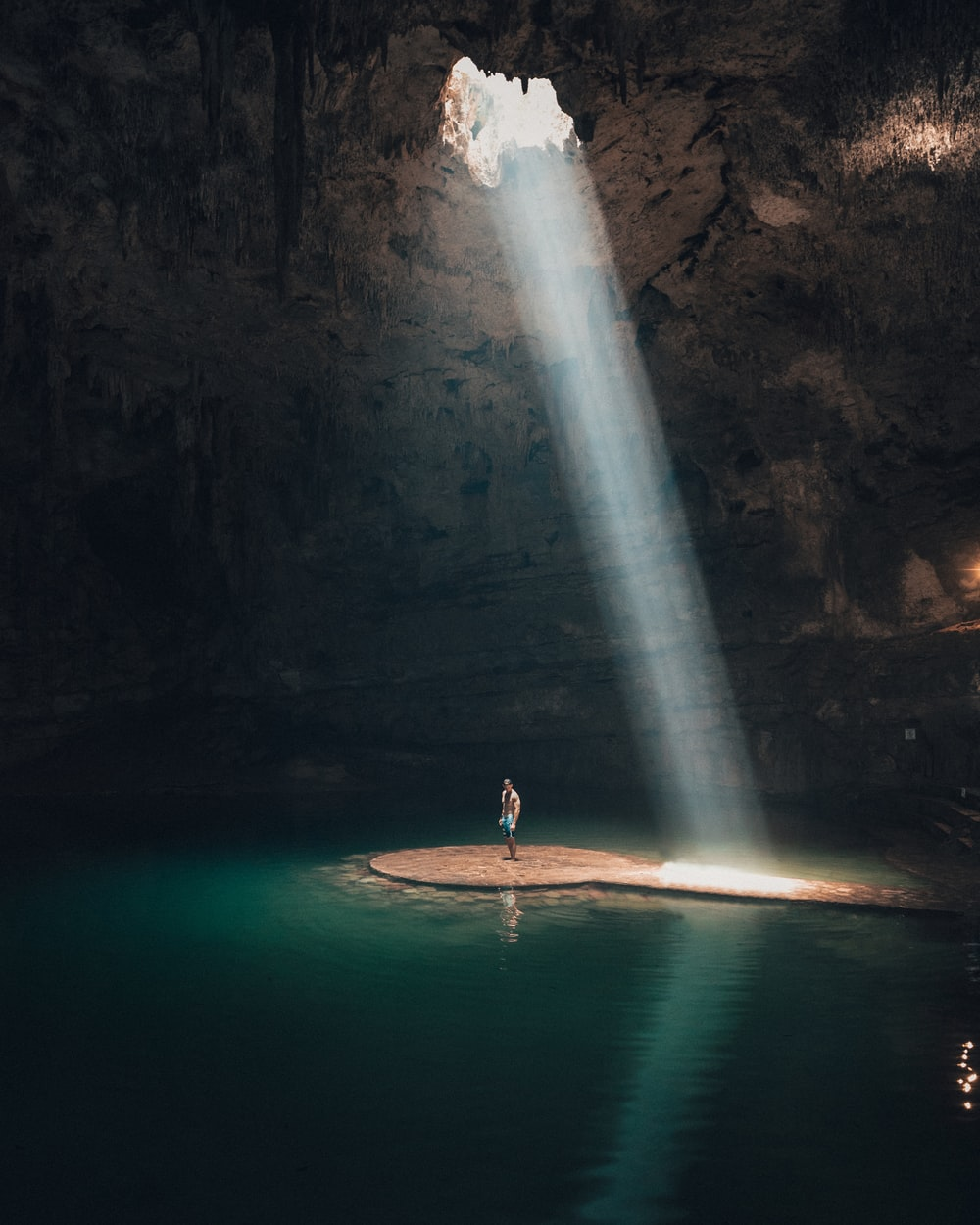 photo of man standing in cave surrounded by water