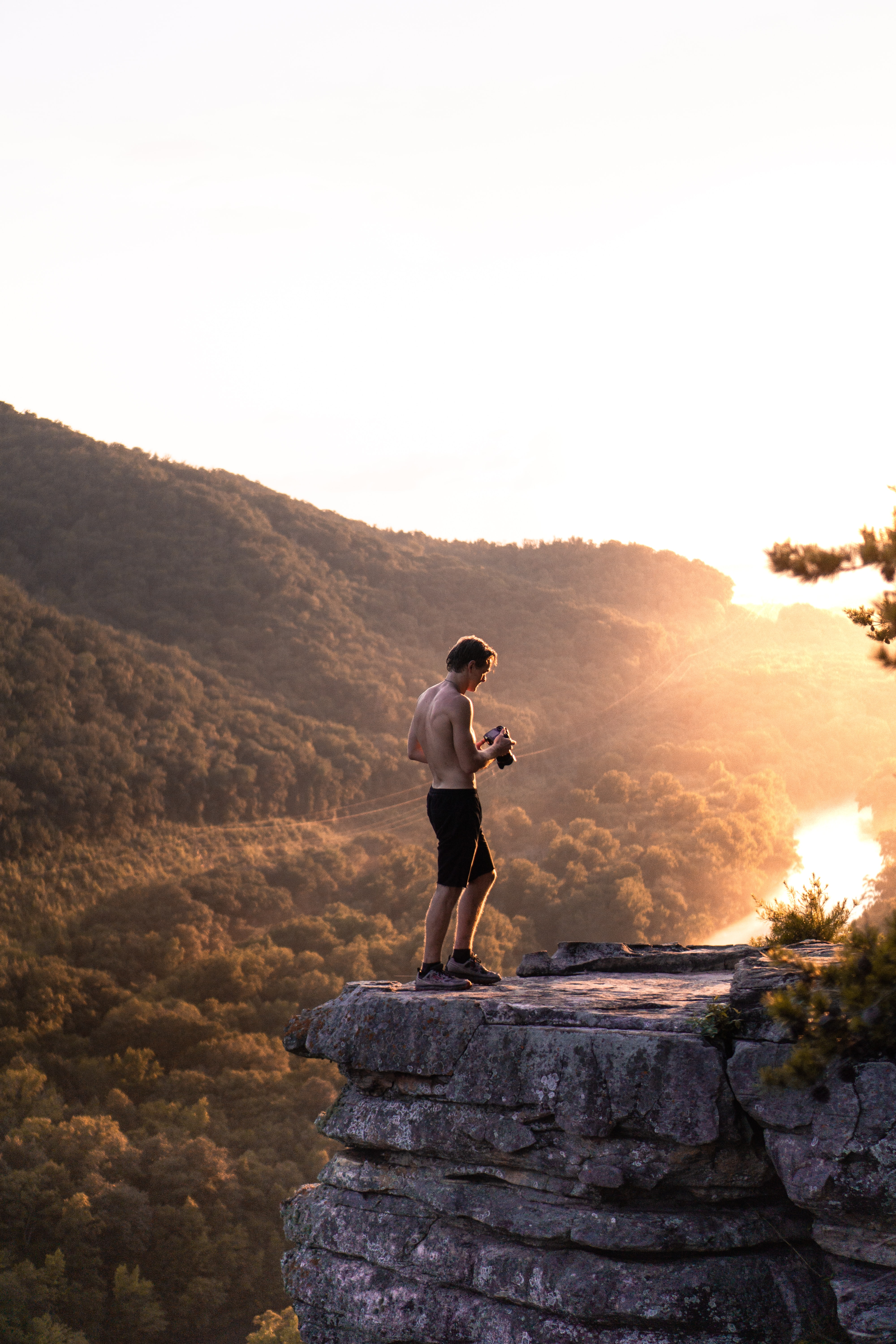 topless man in black shorts standing near cliff at daytime