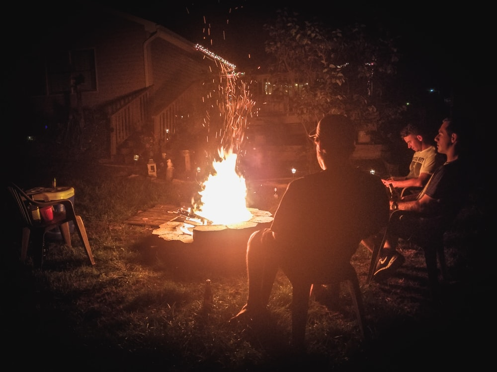 three men in front of bonfire