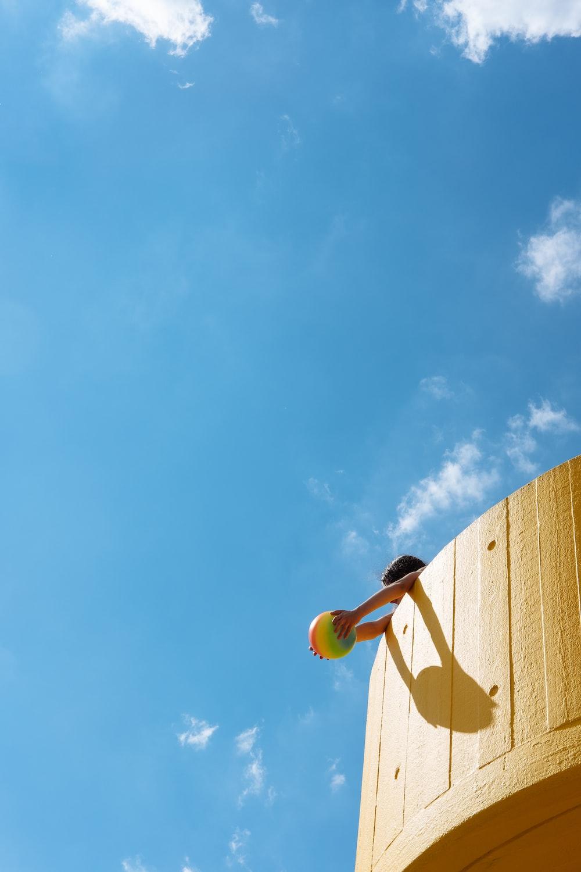 toddler holding ball under blue sky