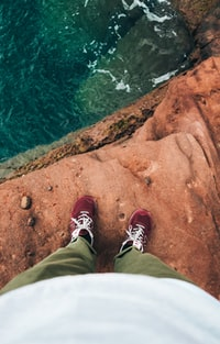 person standing on rock formation in front of body of water