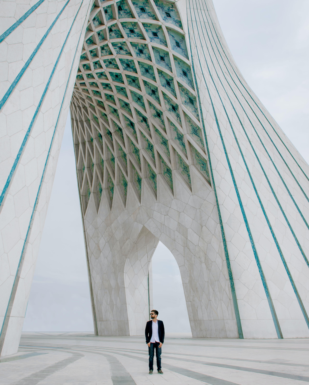 man standing under arch building