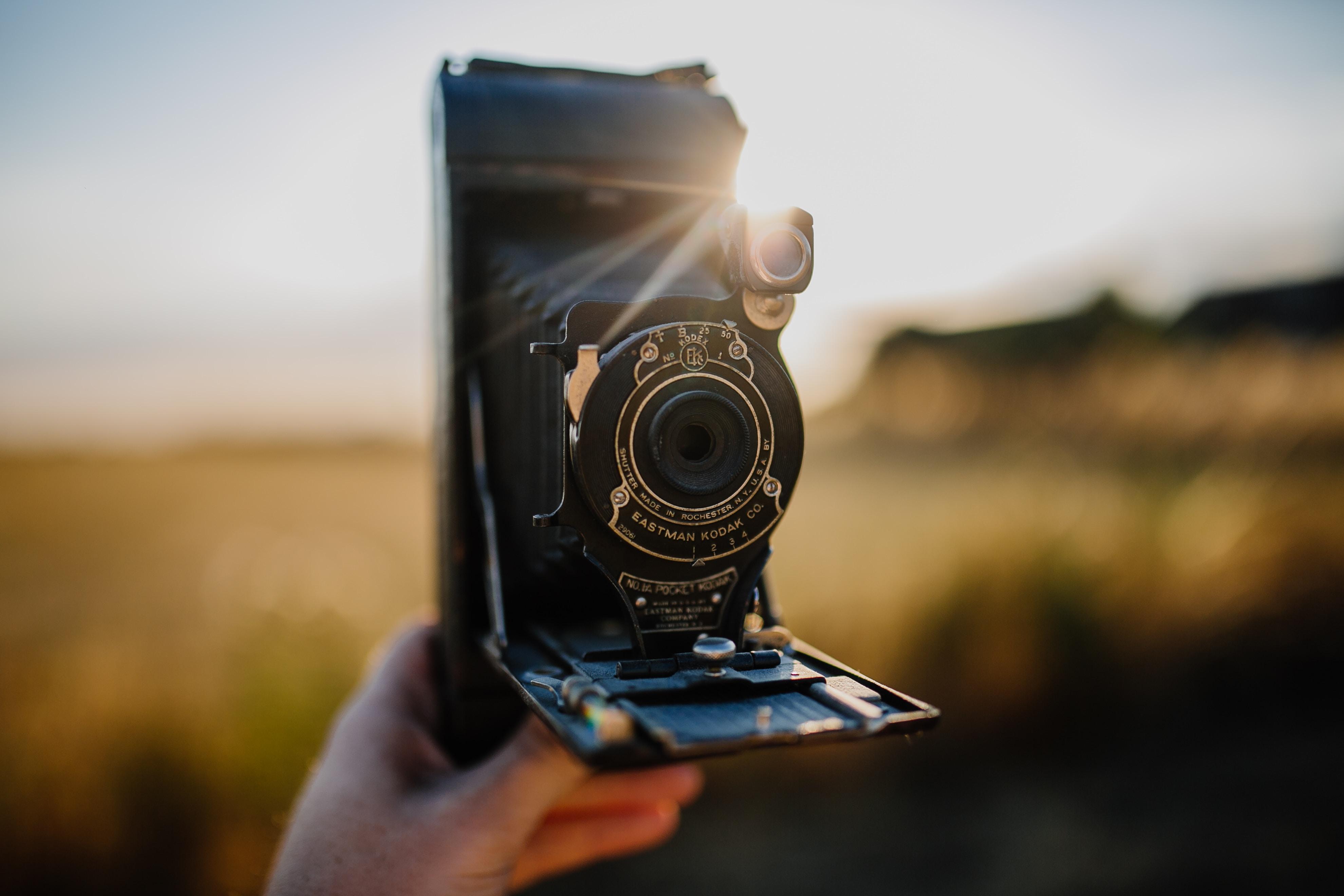 person holding black folding camera