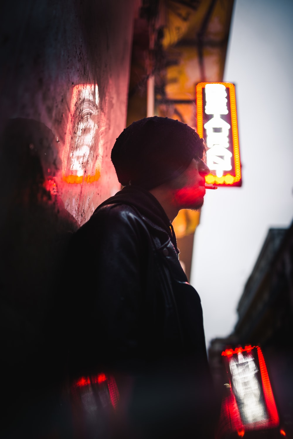 man leaning on wall under neon sign