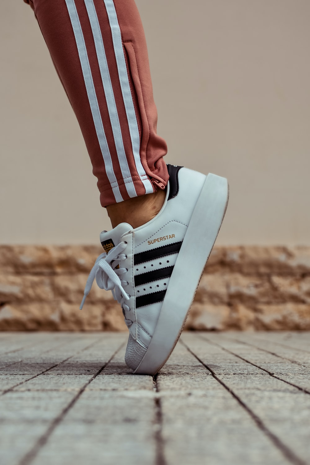 lowest price 65966 4df19 person wearing white and black adidas Superstar sneaker