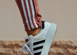 person wearing white and black adidas Superstar sneaker