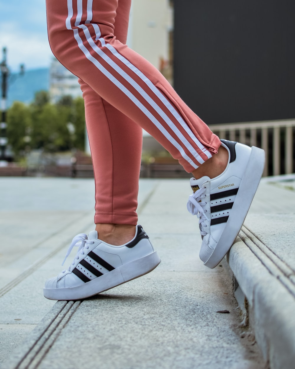 554ba505d8db person in white adidas Superstar walking on stair