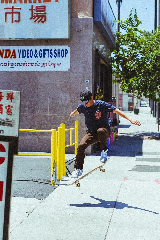 man in blue shirt skateboarding on gray surface