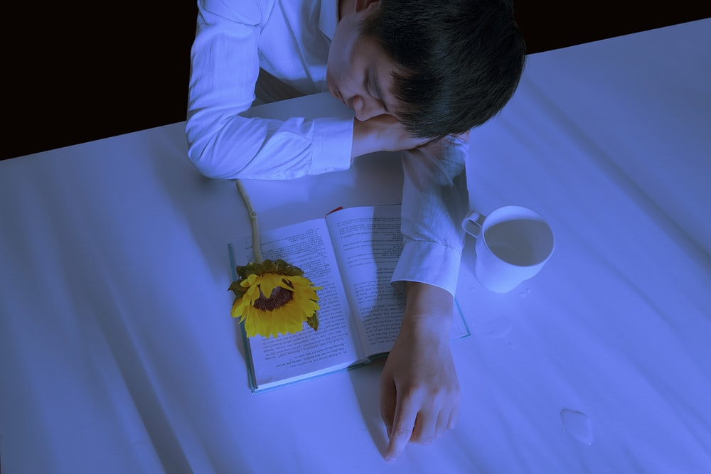 man in white dress shirt leaning on table beside book and mug