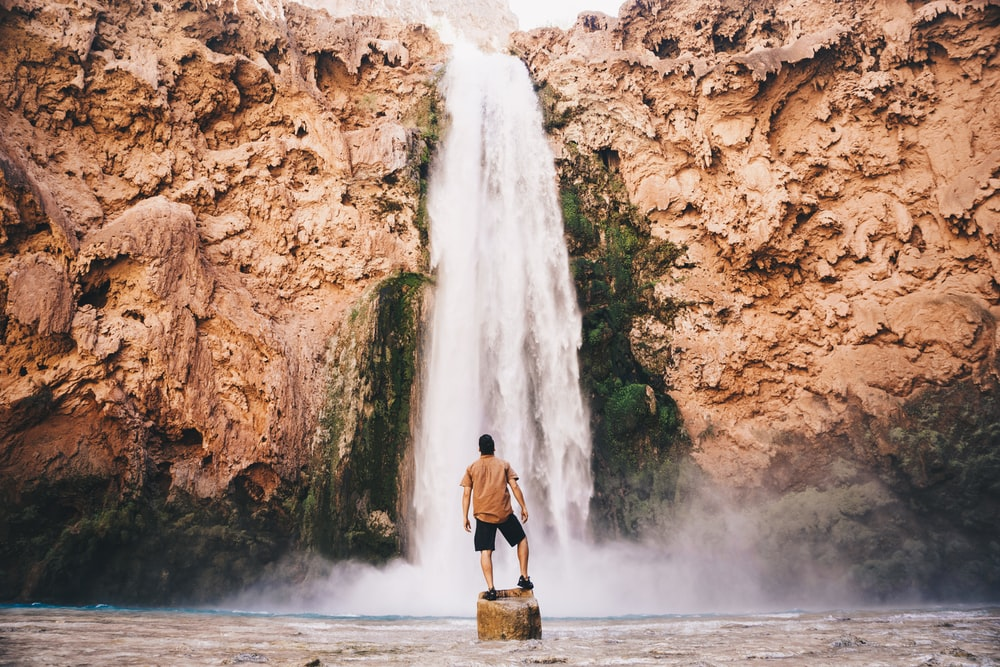 man standing on stone in front of waterfall