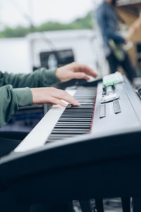man playing black and white electronic keyboard