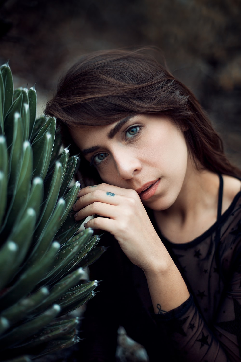 woman leaning on green plant