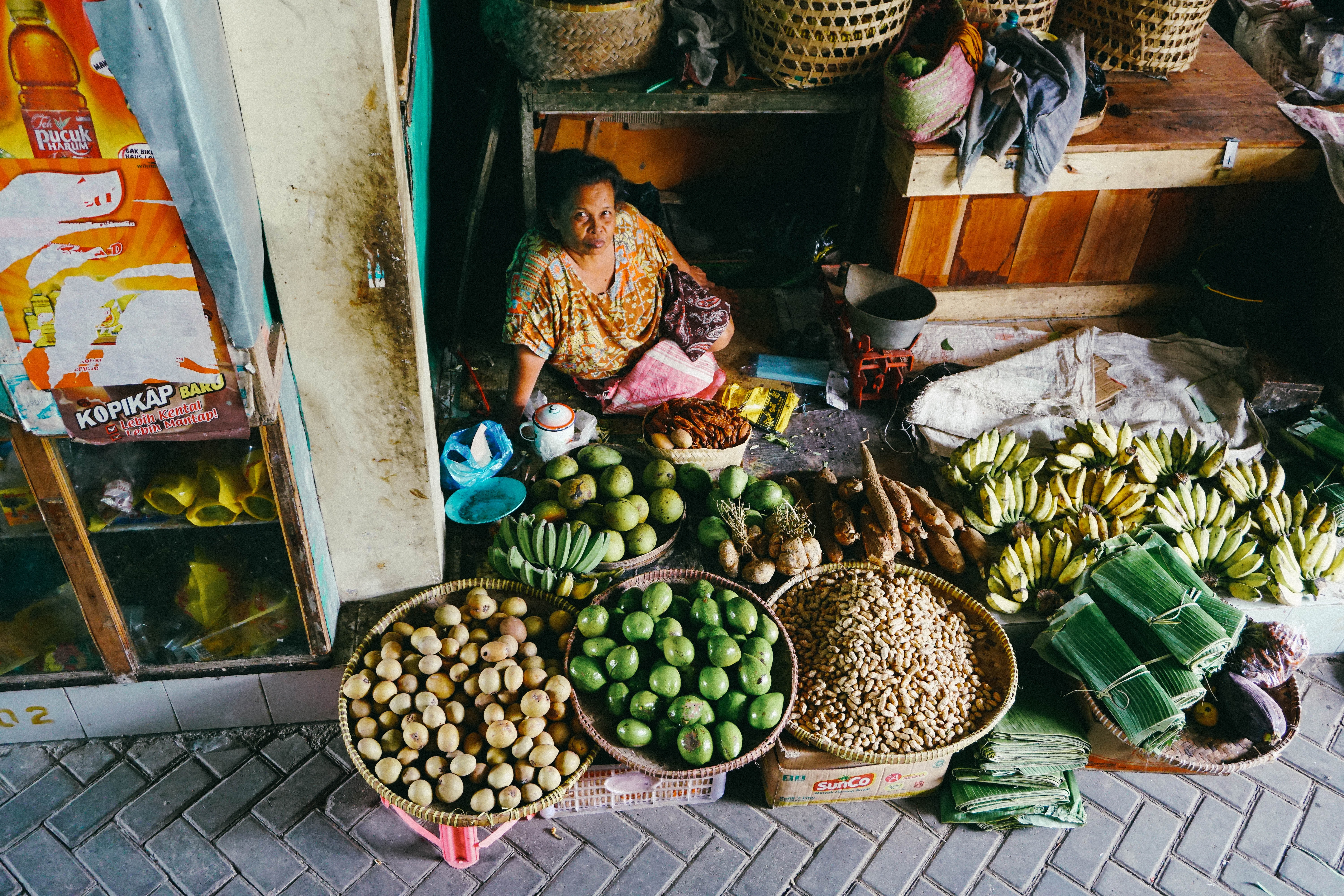 woman sitting beside fruits on display baskets