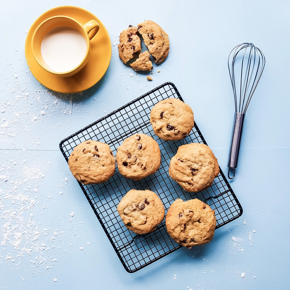 cookies on black grill beside yellow ceramic cup