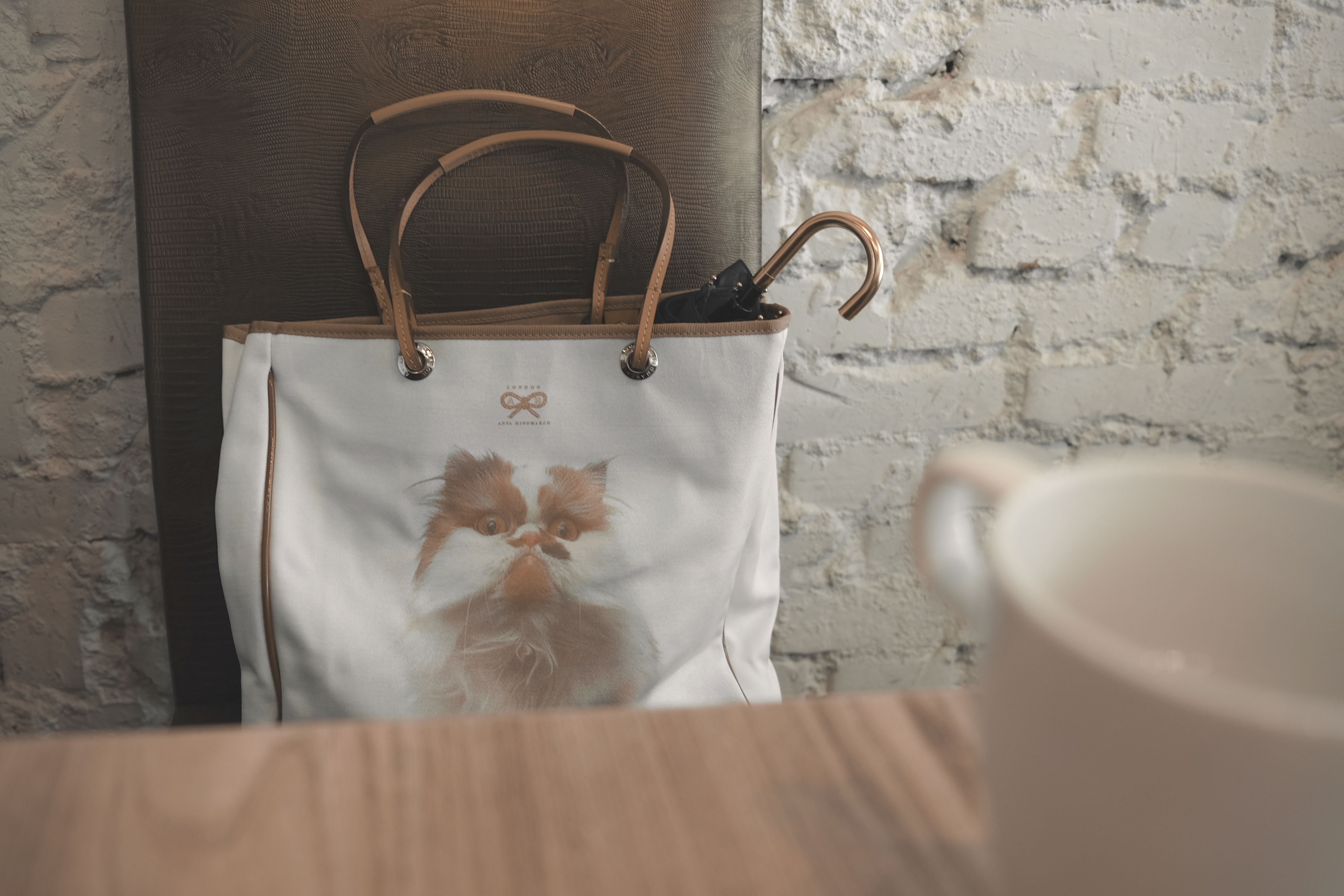 white and brown leather tote bag on chair